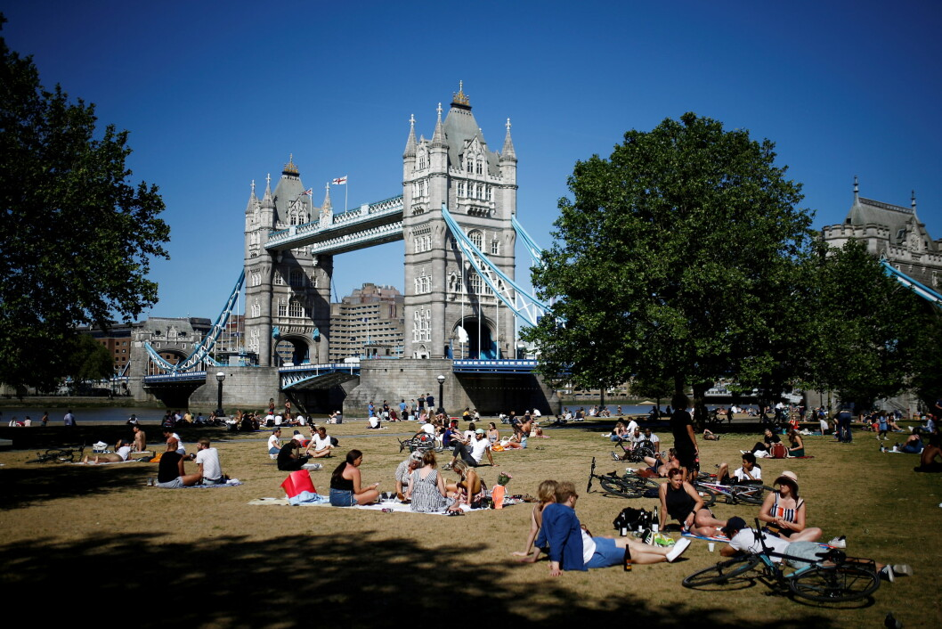 FILE PHOTO: People sit down in the hot weather infront of Tower Bridge, following the outbreak of the coronavirus disease (COVID-19), London, Britain, May 28, 2020. REUTERS/Henry Nicholls/File Photo