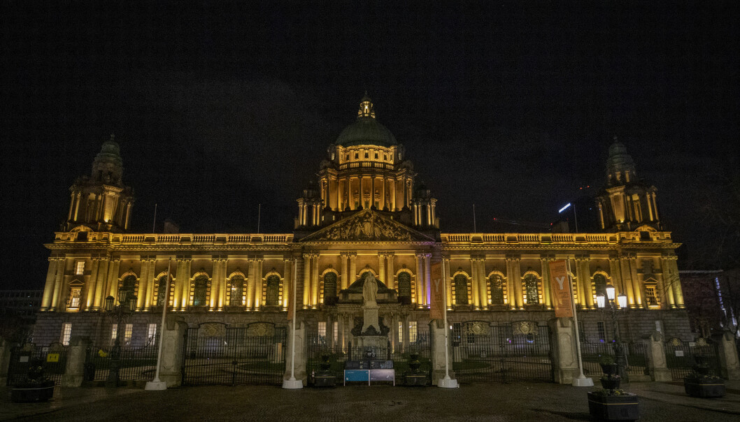 Belfast City Hall which is illuminated in yellow to mark the National Day of Reflection. Picture date: Tuesday March 23, 2021.