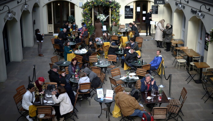 People sit at outside restaurant area, as the coronavirus disease (COVID-19) restrictions ease, at Covent Garden in London, Britain April 12, 2021. REUTERS/Henry Nicholls/File Photo