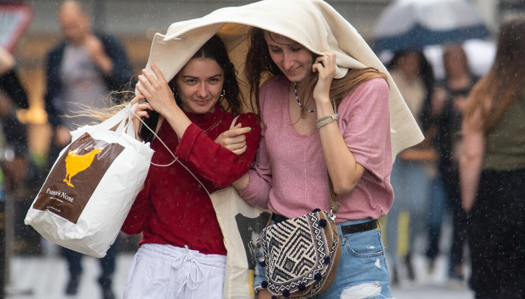 Two women take shelter under a coat during a sudden downpour of rain in Covent Garden, London, as parts of the UK are hit by heavy rain and thunderstorms. Picture date: Sunday July 4, 2021.