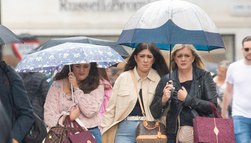 People shelter under umbrellas during a downpour of rain in Covent Garden, London, as parts of the UK are hit by heavy rain and thunderstorms. Picture date: Sunday July 4, 2021.