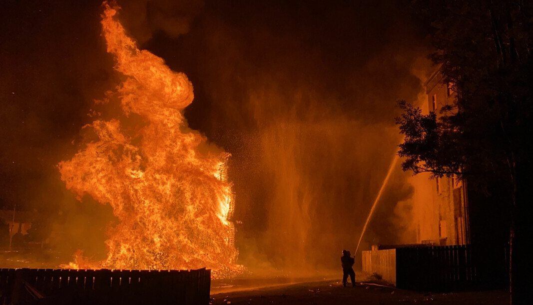 A member of the Fire Service dampens down nearby flats as huge bonfire burns in the loyalist Corcrain area of Portadown.