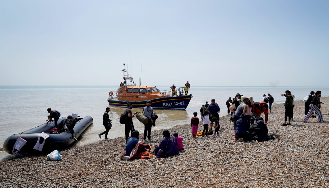 People thought to be migrants make their way up the beach after arriving on a small boat at Dungeness in Kent. Picture date: Monday July 19, 2021.