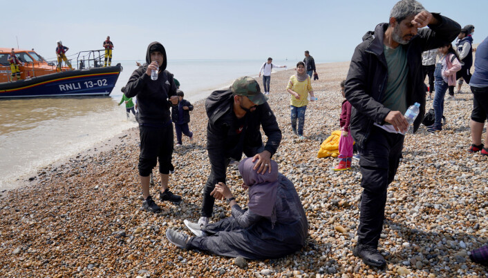 A man helps a woman as a group of people thought to be migrants make their way up the beach after arriving on a small boat at Dungeness in Kent. Picture date: Monday July 19, 2021.