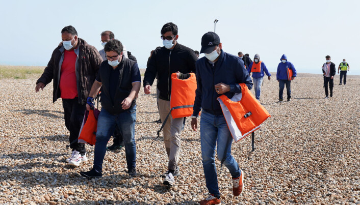 A group of people thought to be migrants crossing from France are escorted by officials from the beach at Dungeness, Kent, following a small boat incident in the Channel. Picture date: Tuesday July 20, 2021.
