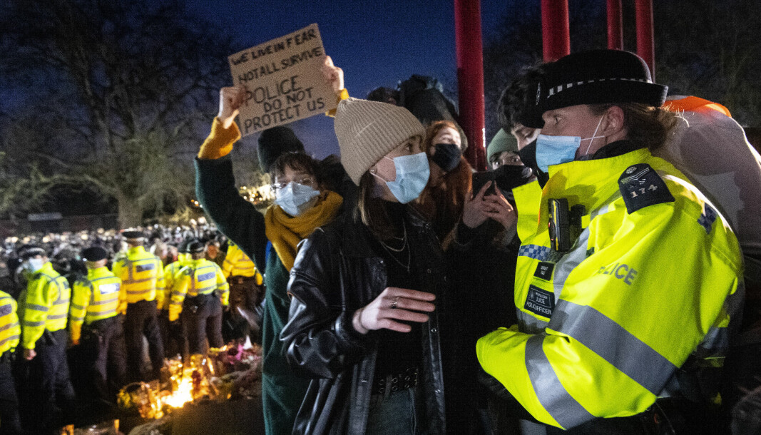 A woman talks to a police officer during a gathering in Clapham Common, London, after the Reclaim These Streets vigil for Sarah Everard was officially cancelled.