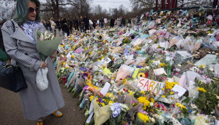 A woman holding flowers looks at floral tributes left at the bandstand in Clapham Common, London, for Sarah Everard. Pc Wayne Couzens, 48, appeared at the Old Bailey in London charged with the kidnap and murder of the 33-year-old. Picture date: Sunday March 21, 2021.