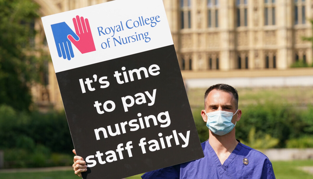 A Nurse with a placard outside the Royal College of Nursing (RCN) in Victoria Tower Gardens.