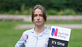 Amy Fancourt with a placard outside the Royal College of Nursing (RCN) in Victoria Tower Gardens.