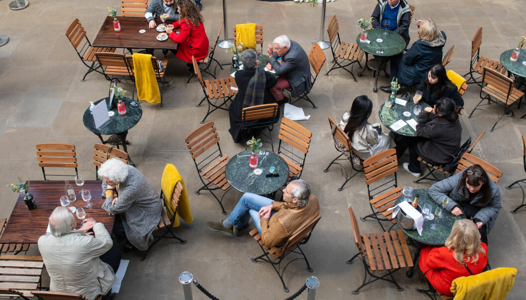 People eat and drink outside a restaurant in Covent Garden Market, London, following the further easing of lockdown restrictions.