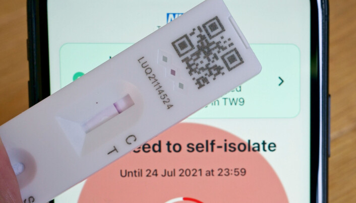 A negative lateral flow test next to advice from the NHS COVID app on an iphone to self isolate.