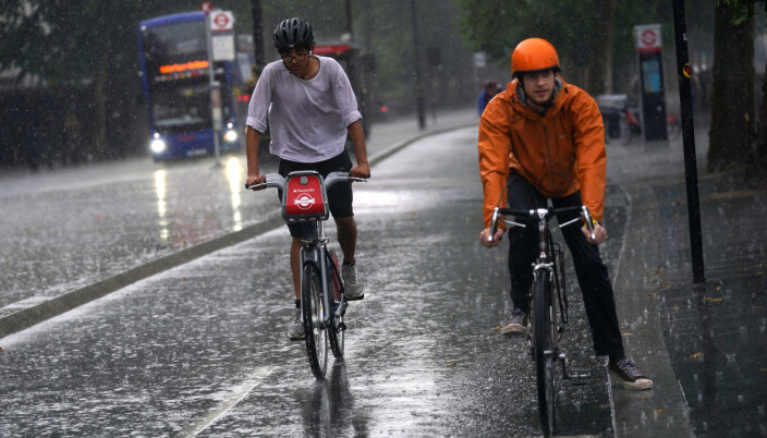 Two cyclists ride along the Embankment as heavy rain sweeps through central London.
