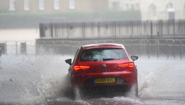 A car drives through flood water in Horse Guards Road in central London.