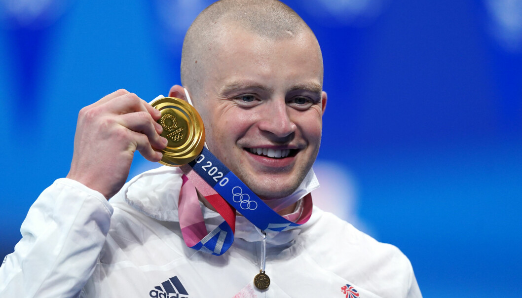Great Britain's Adam Peaty poses with his gold medal on the podium after winning the Men's 100m Breaststroke final at the Tokyo Aquatics Centre on the third day of the Tokyo 2020 Olympic Games in Japan. Picture date: Monday July 26, 2021.