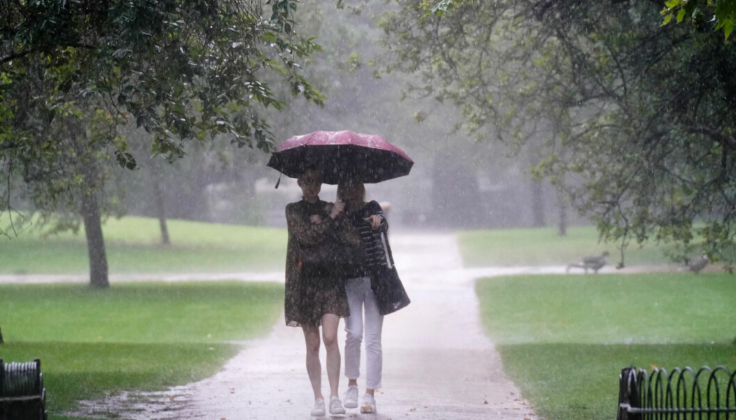 Two women walks through heavy rain in St James's Park in central London. Thunderstorms bringing lightning and torrential rain to the south are set to continue until Monday, forecasters have said. Picture date: Sunday July 25, 2021.