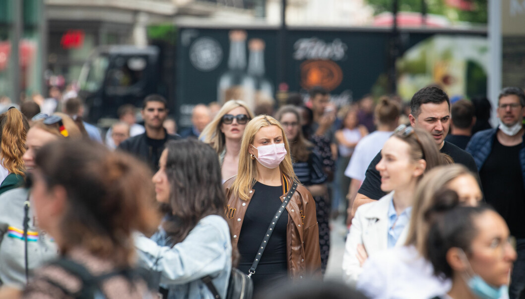 A woman wearing a face mask among a crowd of pedestrians on Oxford Street, London.