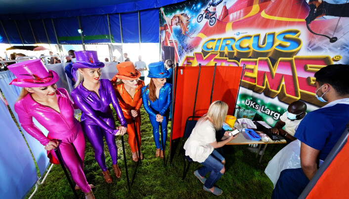 Performers from Circus Extreme watch as Rhiannon Alexander, 34 from Bradford, waits to have a Covid-19 vaccination at a pop-up vaccination clinic in the marquee of the circus in Halifax.