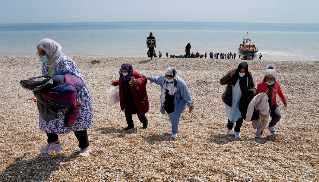 People thought to be migrants making their way up the beach after arriving on a small boat at Dungeness in Kent.