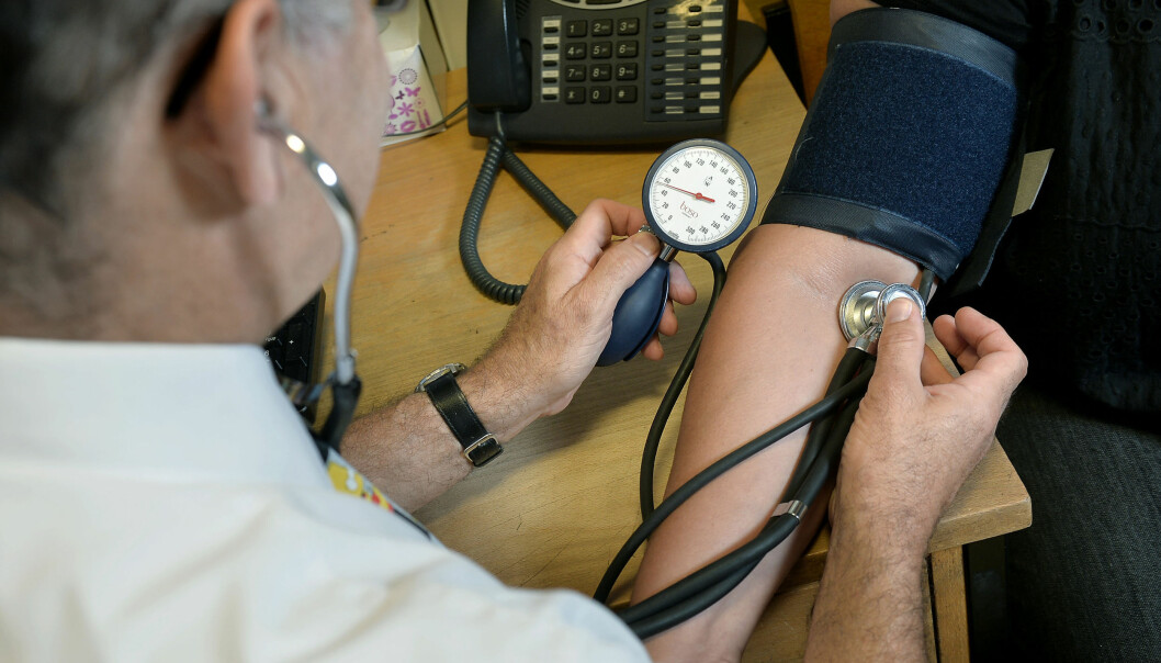 GP checking a patient's blood pressure.
