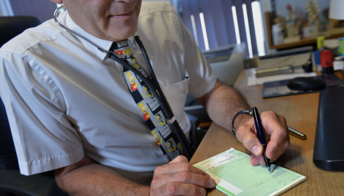 Dr Laurence Buckman writes a prescription in his practice room at the Temple Fortune Health Centre GP Practice near Golders Green, London.