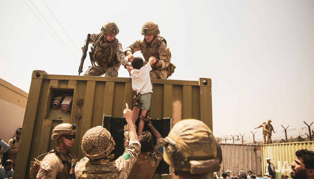 UK coalition forces, Turkish coalition forces, and U.S. Marines assist a child during an evacuation at Hamid Karzai International Airport, Kabul, Afghanistan.