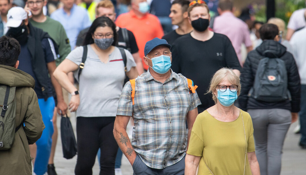 People wearing face masks among crowds of pedestrians in Covent Garden, London.