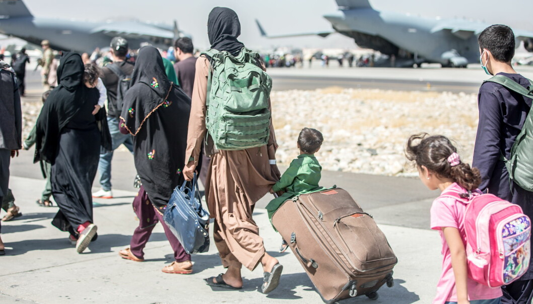 A woman pulls a suitcase with a child sitting on top during an evacuation at Hamid Karzai International Airport, Kabul, Afghanistan.