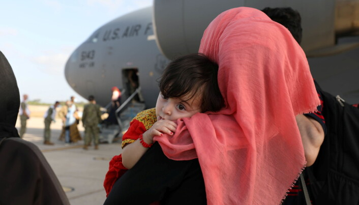 Part of group of 450 Afghan citizens who have been evacuated from Kabul watch as other compatriots leave a U.S. Air Force C-17 Globemaster III transport plane after arriving from Kuwait, at Naval Station (NAVSTA) Rota Air Base in Rota, southern Spain, August 27, 2021.