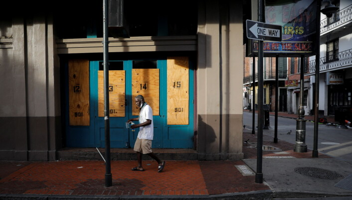 A man walks past boarded up windows in Bourbon Street at the French Quarter after Hurricane Ida made landfall in Louisiana.