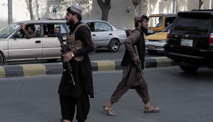 Taliban fighters guard a check-point on a main street in Kabul.
