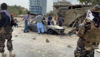 Afghan men take pictures of a vehicle from which rockets were fired, as Taliban forces stand guard, in Kabul.
