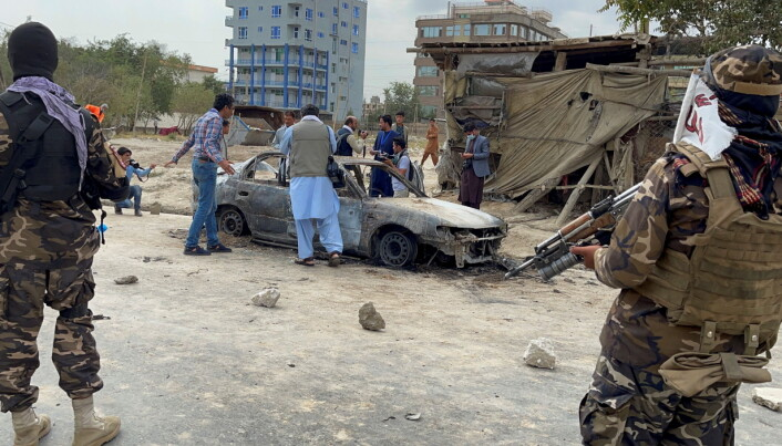 Afghan men take pictures of a vehicle from which rockets were fired, as Taliban forces stand guard, in Kabul, Afghanistan August 30, 2021. REUTER/Stringer  NO RESALES. NO ARCHIVES