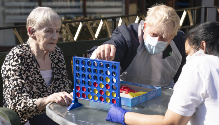 Prime Minister Boris Johnson plays Connect 4 with resident Janet (left) and carer Lakshmi during a visit to Westport Care Home in Stepney Green, ahead of unveiling his social care reform plan.