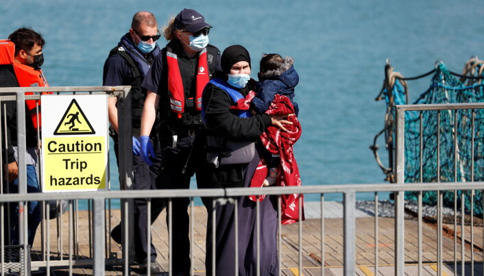 A migrant, rescued from the English Channel, walks holding a child in Dover