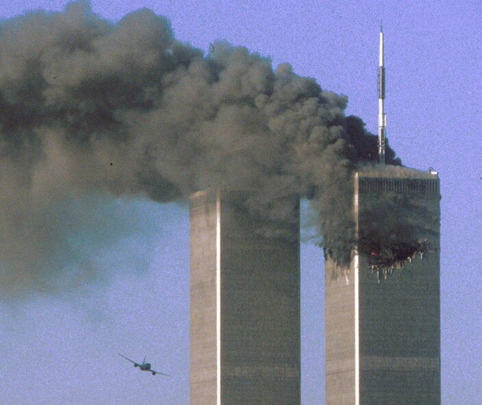 Hijacked United Airlines Flight 175 flies toward the World Trade Center twin towers shortly before slamming into the South tower (L), as the North tower burns, following an earlier attack by a hijacked airliner in New York, U.S., September 11, 2001.
