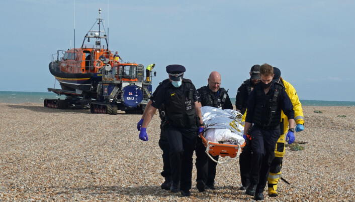 Police officers and members of the RNLI carry an person from a boat after a group of people thought to be migrants were brought into Dungeness, Kent.