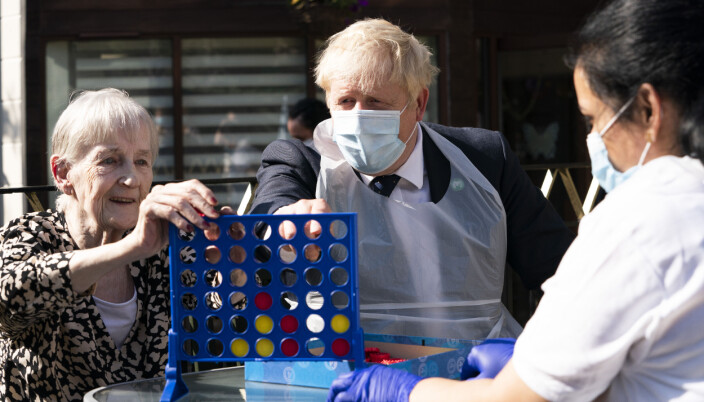 Prime Minister Boris Johnson plays Connect 4 with resident Janet (left) and carer Lakshmi during a visit to Westport Care Home in Stepney Green, east London.