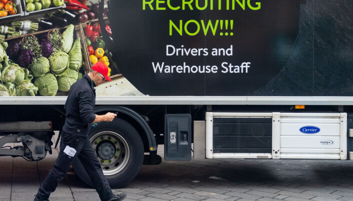 An advert for drivers and warehouse staff on the side of a lorry as a driver makes a delivery in central London.